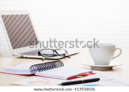Office workplace with laptop, coffee cup, reports and notepad on desk table in front of window with blinds - stock photo