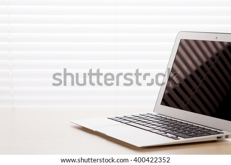 Office workplace with laptop on desk table in front of window with blinds - stock photo