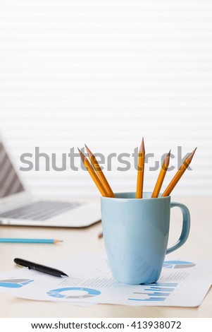 Office workplace with laptop, reports and pencils on wooden desk table in front of window with blinds - stock photo