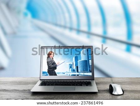 Office workplace with laptop with businesswoman on screen - stock photo
