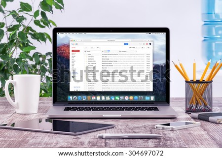 Office workplace with open Apple Macbook Pro Retina with Google Gmail web page on the display. Gmail is a most popular free Internet e-mail service provided by Google. Varna, Bulgaria - May 31, 2015. - stock photo