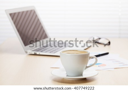 Office workplace with with laptop and coffee cup on wooden desk table in front of window with blinds - stock photo