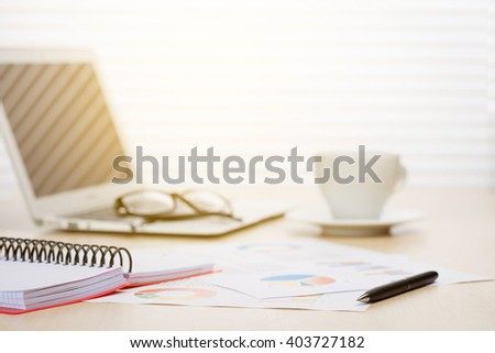 Office workplace with with laptop and coffee on wooden desk table in front of window with blinds. Sunset light. Focus on pen - stock photo