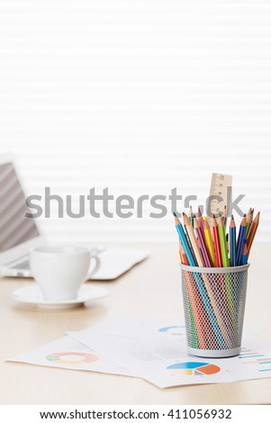 Office workplace with with laptop, colorful pencils and coffee cup on wooden desk table in front of window with blinds - stock photo