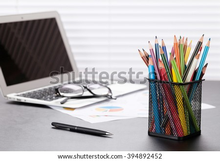 Office workplace with with laptop, reports and pencils on wooden desk table in front of window with blinds - stock photo