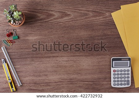 Office Workspace. Top View of a Business Workplace. Wooden Desk Table, Paper Cutter, Ruler, Calculator, Envelope, Plant Pot, Clips. Copy space for text or Image - stock photo