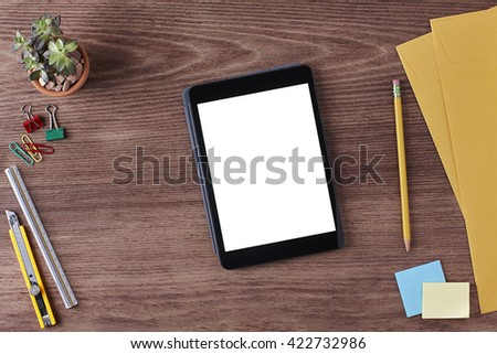 Office Workspace. Top View of a Business Workplace. Wooden Desk Table, Paper Cutter, Ruler, Pen, Pencil, a Blank Screen Tablet, Envelope, Plant Pot, Clips. Copy space for text or Image