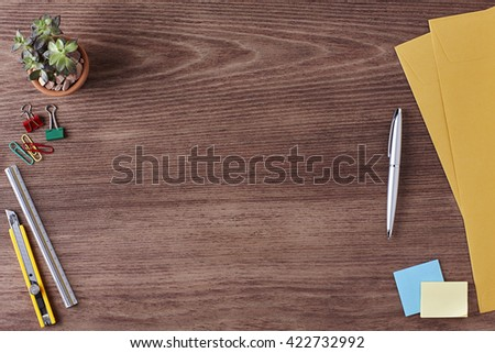 Office Workspace. Top View of a Business Workplace. Wooden Desk Table, Paper Cutter, Ruler, Pen, Envelope, Plant Pot, Clips. Copy space for text or Image - stock photo