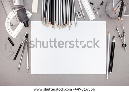 office workspace with blank paper, pencils and various drawing tools, top view