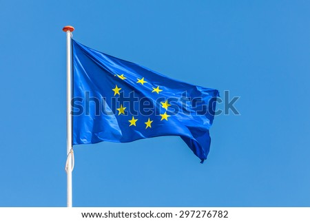 Official flag of the European Union in front of a clear blue sky - stock photo