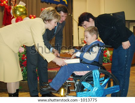 official persons donate the prize for disabled kid - stock photo