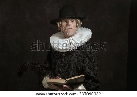 Official portrait of historical governor from the golden age. Writing in book. Studio shot against dark wall. - stock photo