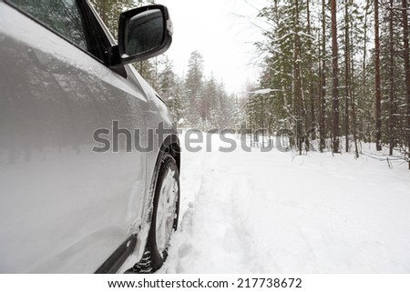 Offroad car standing on snowy forest road, copyspace - stock photo