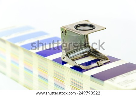 Offset print concept. Magnifying loupe glass standing on panthone test palette - stock photo