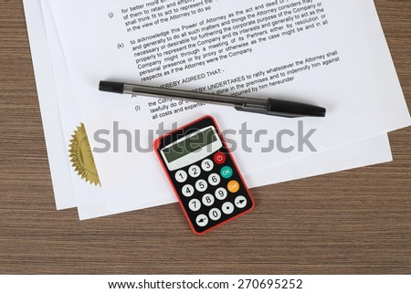 "Offshore finances and online banking security concept - digital password generation device with pen lies over standard ""power of attorney"" document on writing desk  - stock photo"