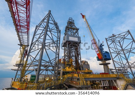 offshore jack-up oil and gas drilling rig with crane operation - stock photo