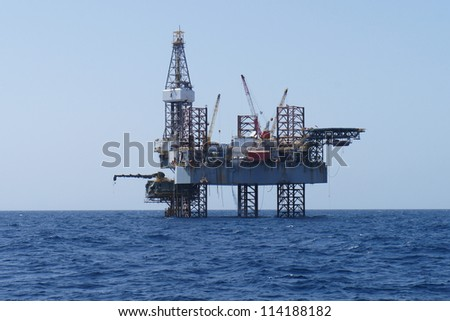 Offshore Jack Up Oil Drilling Rig and The Production Platform - stock photo