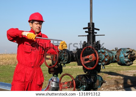 Offshore Oil Rig Operator.Oil worker in safety gear with hand tool working on oil rig equipment. - stock photo