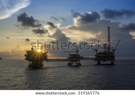 Offshore oil rigs or production platforms during sunset - stock photo