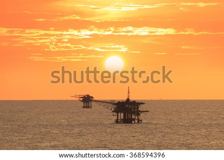 Offshore platform in the middle of the ocean with beautiful sunset - stock photo