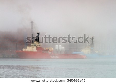 Offshore supply vessel moving in the fog. - stock photo