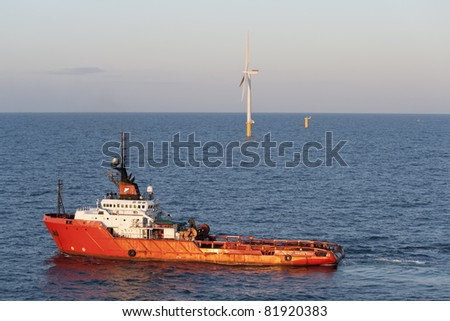Offshore Wind Turbine and a anchor handling tug in a Windfarm under construction  off the English Coast - stock photo
