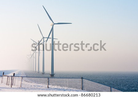 Offshore windturbines in the Dutch sea, disappearing in the winter haze; in front a fence covered by hoar frost - stock photo
