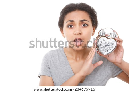 Oh my god. Portrait of youthful pleasant mulatto girl holding alarm clock near her face on white isolated background.