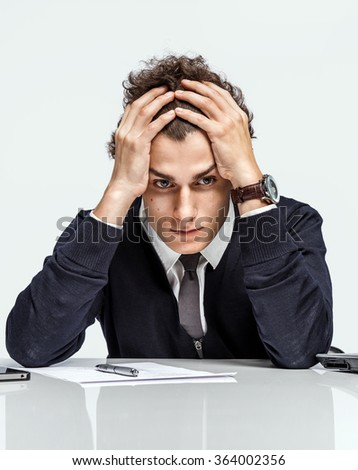 Oh my god, stressed businessman is taken for the head / modern office man at working place on grey background. Depression and crisis concept - stock photo