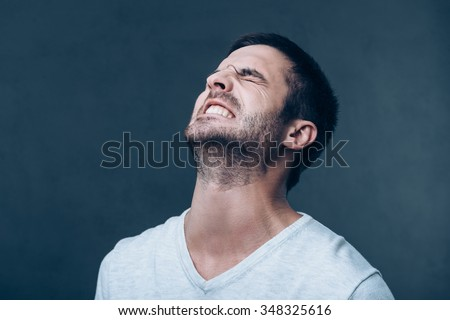 Oh no! Frustrated young man keeping eyes closed and expressing negativity while standing against grey background - stock photo