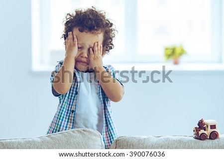 Oh no! Little African baby boy crying and rubbing his eyes while standing on the couch at home  - stock photo