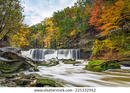 Ohio's Great Falls of Tinker's Creek is surrounded by a beautiful display of fall foliage color. - stock photo