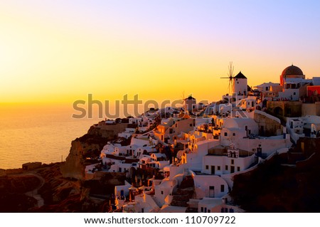 OIA, SANTORINI, GREECE - JULY 10: Sunset at Oia village on July 10, 2010 in Santorini, Greece. Santorini is that remains after an enormous volcanic explosion and created the current geological caldera - stock photo