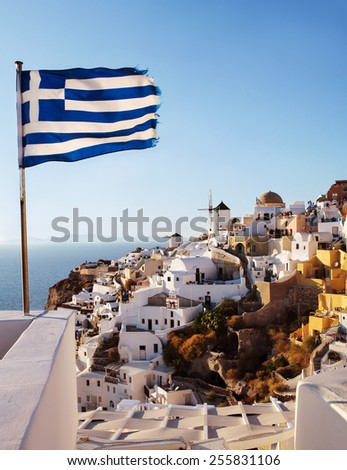 Oia, Santorini. View of famous windmill on cliff side, and Greek flag. - stock photo