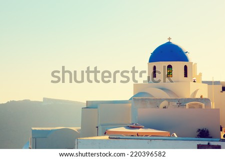 Oia town on Santorini island, Greece at sunset. Traditional and famous church with blue domes over the Caldera, Aegean sea - stock photo