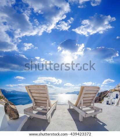 Oia village with sunbeds on Santorini island in Greece - stock photo
