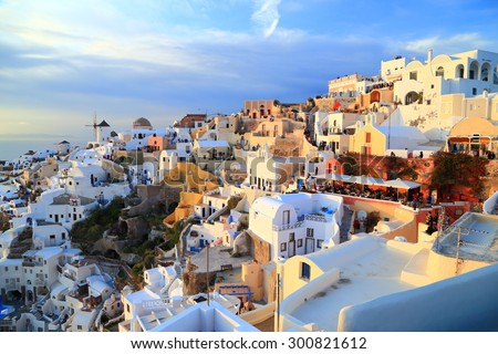 Oia village with white buildings illuminated by the sunset light, Santorini island, Greece