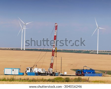 Oil and Gas Drilling Equipments with Wind turbine on background. Exploitation of the two sources of energy.