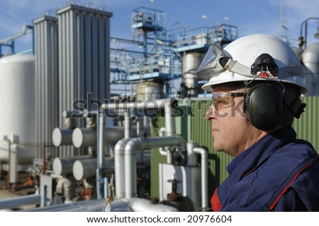 oil and gas engineer in focus, large refinery industry in background - stock photo