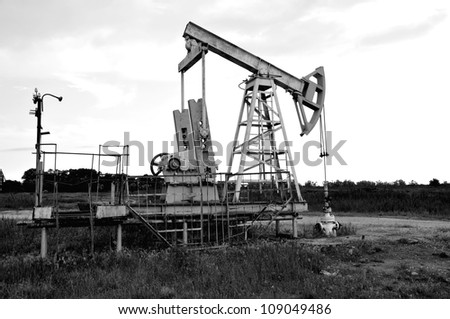 Oil and gas industry: old rusty oil pump jack on a oil field (black and wite)