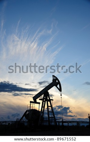 Oil and gas industry. Silhouette oil pump on a sunset sky background. - stock photo