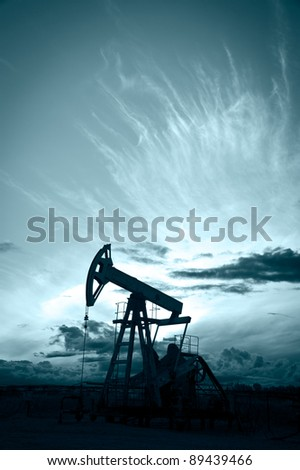 Oil and gas industry. Silhouette oil pump on a sunset sky background. Toned. - stock photo