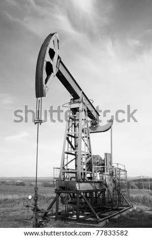 Oil and gas industry. Work of oil pump jack on a field. Environment damage. Black and white photo - stock photo