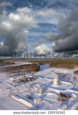 Oil and gas industry. Work of oil pump jack on a oil field.. Construction site in wild winter forest. Building of petrochemical plant - stock photo