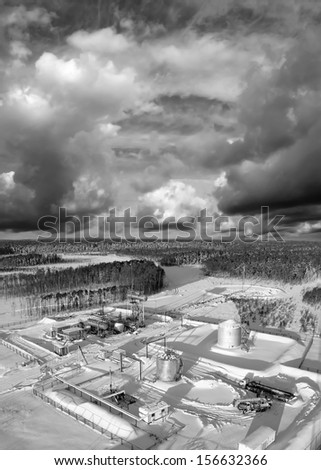 Oil and gas industry. Work of oil pump jack on a oil field.. Construction site in wild winter forest. Building of petrochemical plant. Black and white photo - stock photo