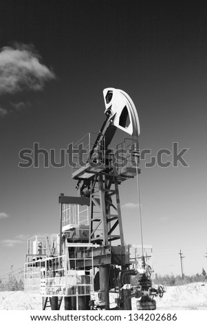 Oil and gas industry. Work of oil pump jack on a oil field in desert. Black and white photo