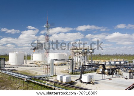 Oil and gas industry. Work of refinery petrochemical plant. Oil reservoir and storage tank of mineral oil. Flame torch - stock photo