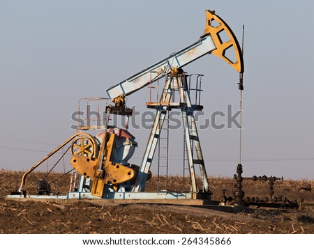 Oil and gas pump operating in agricultural area in Europe - stock photo