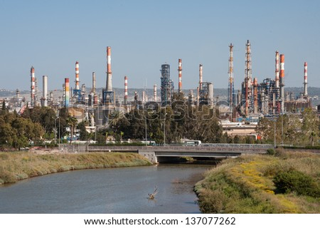 Oil and gas refinery plant with river on the foreground - stock photo