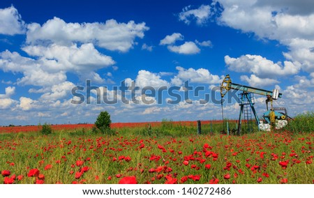 Oil and gas well in rural countryside with poppy field - stock photo